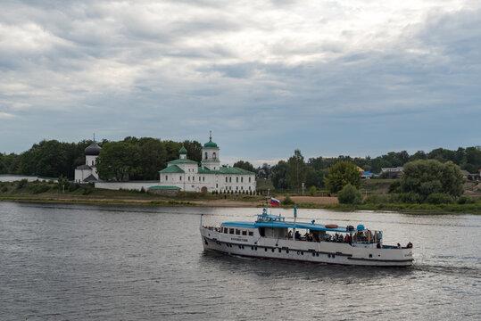 Pleasure boat on the river Velikaya opposite The Mirozhsky monastery. Spaso-Preobrazhensky Cathedral (12th century) and Stefanovskaya Church (17th century), Pskov, Russia