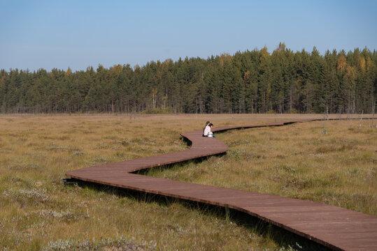 People seated on wooden walkway on the territory of Sestroretsk swamp reserve. Saint-Petersburg. Russia