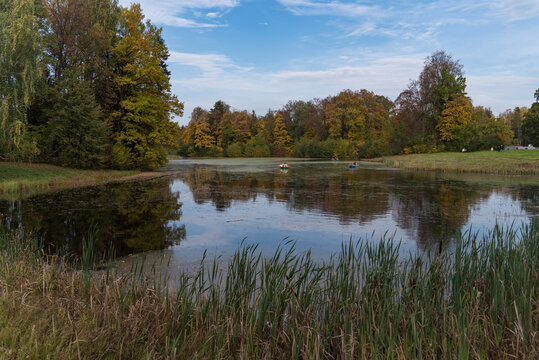 Tourists float on boat in Pavlovsk park in fall, St. Petersburg, Russia