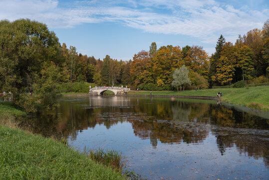Vintage Viskontiev bridge over Slavyanka river. The autumn landscape. Pavlovsk Palace Park. Saint-Petersburg, Russia