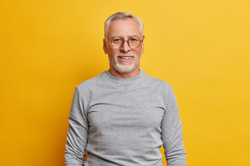 Glad grey haired man with satisfied expression has good mood wears optical glasses and casual...