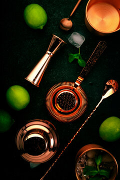 Copper bar tools and bartender accessories for making cocktail. Shaker, jigger, strainer, spoon. Alcohol drinks and beverages preparation. Black background, top view