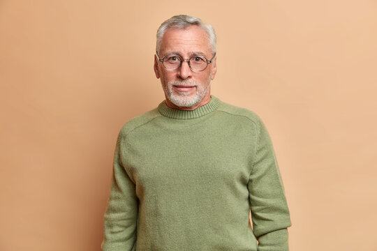 Handsome bearded European man with curious gaze wears spectacles and basic jumper looks directly at camera poses against beige background. Self confident successful senior entrepreneur indoor