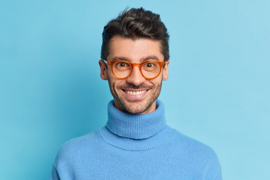Headshot of handsome bearded with European appearance looks directly at camera smiles pleasantly feels happy wears casual turtleneck poses indoor. Glad student glad to pass exam successfully
