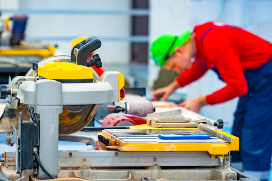 A man in a bright cap working in the Studio. Circular saw for cutting stone and tiles. Finishing work. Circular saw with water supply. Cutting natural stone. Construction equipment.