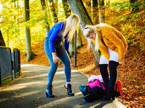 Two women changing shoes in autumn park