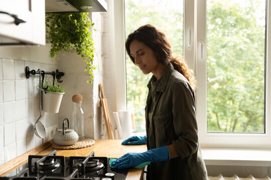 Young Caucasian woman wife in rubber gloves clean polish kitchen stove oven countertop with napkin. Female housekeeper wipe dust do daily household routine with rug. Housekeeping services concept.