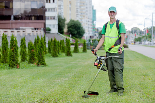 Municipal services senior worker gardener with lawn mover grass trimmer on city street background