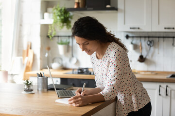 Fototapeta Happy young Caucasian woman stand at home kitchen counter watch webinar on laptop make notes. Smiling female study online on computer at home. Girl make list plan, engaged in time management.