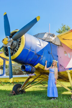A cute woman is standing next to an abandoned plane. A woman with a wreath of flowers on her head