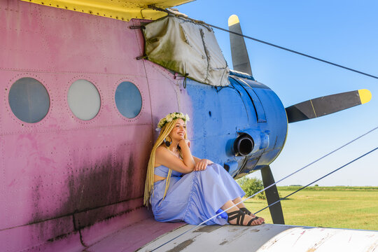 A cute woman is sitting on an abandoned plane. A woman with a wreath of flowers on her head