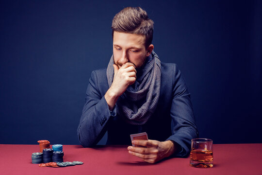 Stylish bearded Man in suit and scarf playing in dark casino, smoking cigar, drink whiskey.
