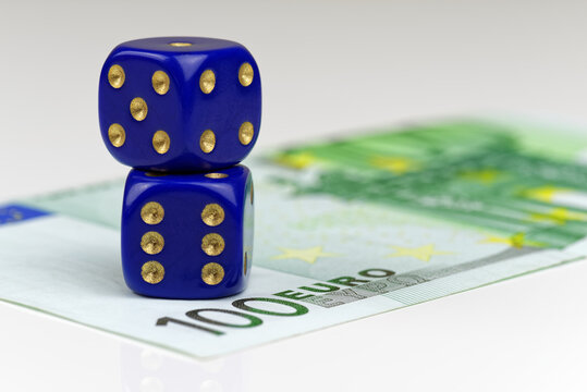 Two blue dices and 100 euro banknote on white background