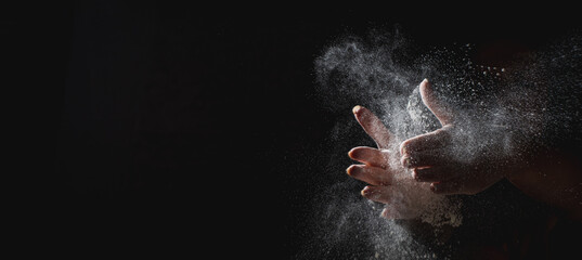 woman chef hand clap with splash of white flour and black background with copy space.