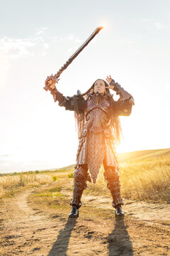 Lady knight in armor with a big sword against the sunset fields background