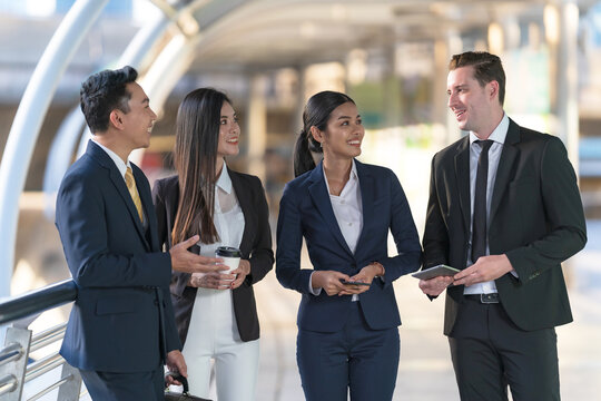 Business people standing and talk to each other in front of modern office