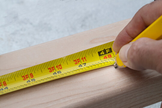 marking four feet on a 2x4 with a measuring tape