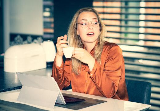 Junge Büroangestellte genießt eine Tasse Kaffee am EDV Arbeitsplatz, Symbolfoto.