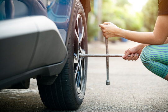 Woman driver with tyre iron changing wheel on a roadside
