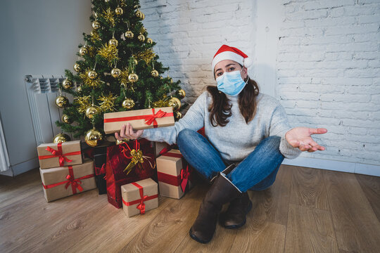 Sad woman with face mask home alone at christmas missing family and friends