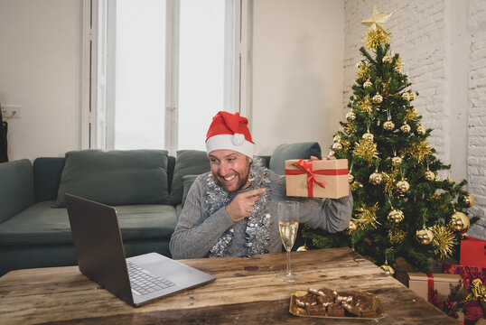 Happy man on video call celebrating virtual christmas with family online at home in lockdown