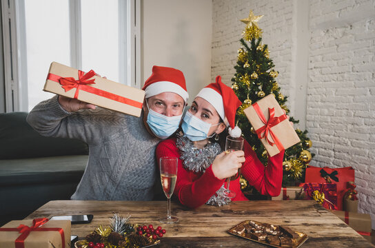 Webcam view of happy couple with face mask on video call celebrating virtual christmas online