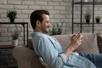Side view addicted to technology happy young man relaxing on comfortable couch with smartphone in...