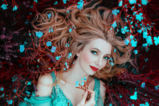beautiful happy fantasy elf woman with blond hair lies dreams on grass, blooming meadow, blue flowers. Portrait smiling face, red lips elegant makeup. Romantic Girl princess resting enjoying life