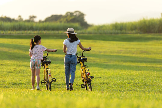 Mother and daughter with bicycling at the garden meadow in sunset near white fence.  Lifestyle Family Concept