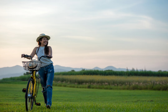 Smiling Asia woman with bicycling at the garden meadow in sunset near mountain background.  Lifestyle  Concept