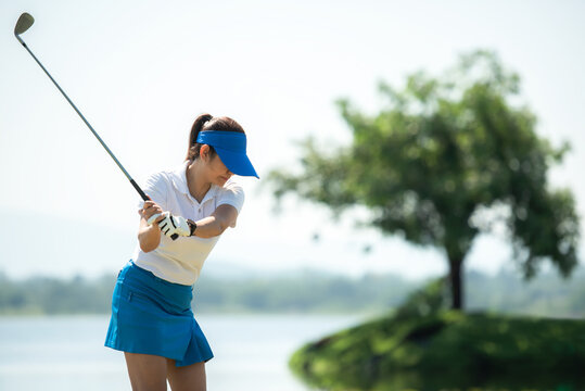 Healthy Sport. Asia golf woman golfer player chips and swing golf on the green Floating water.  people golf presumably does exercise and hobby in holiday. Healthy Lifestyle Concept.
