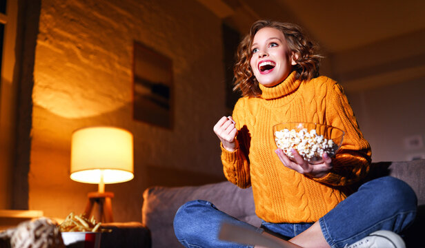 young  delighted cheerful woman with popcorn laughs and watches  movie on  TV   at home in evening  alone.