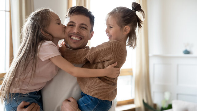 Grateful daughters kiss daddy on cheek, parent receive congrats on Happy Father Day holding hugging two preschool children, laugh looks at camera. Family holiday, single man and adopted kids concept