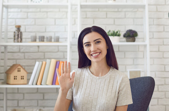 Smiling young woman in sitting on chair in modern office waving hand at camera