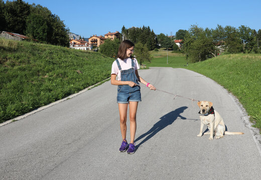 young girl walking the dog on a leash