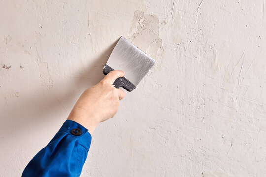 Repairman is finishing wall at home with putty and work tool.