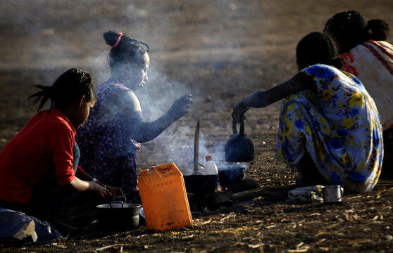 Ethiopians who fled the ongoing fighting in Tigray region, cook in the open in Hamdayet village near the Sudan-Ethiopia border, eastern Kassala state
