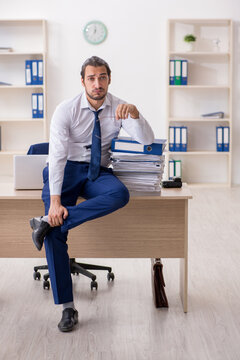 Young businessman unhappy with excessive work in the office