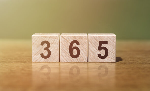 365 word written on wooden blocks on wooden table. New Days 365 New Chances