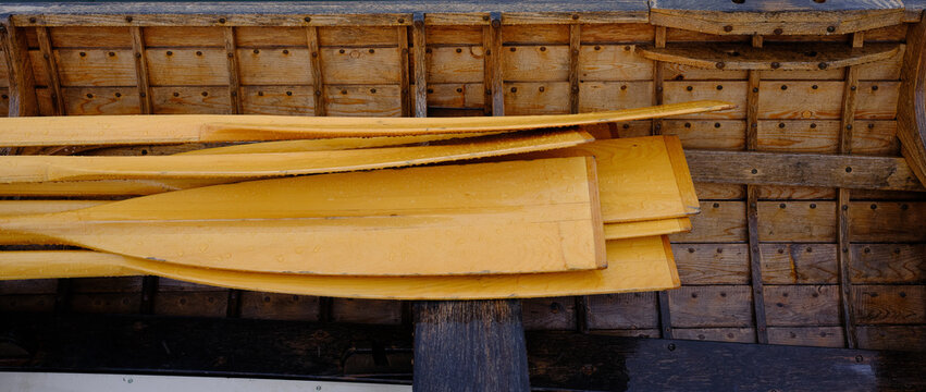 Beautiful warm colored wood of a new rowboat in the rain