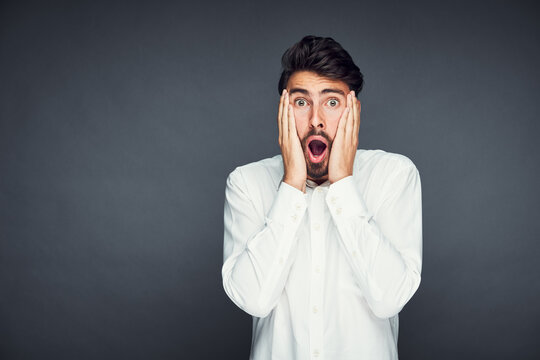 Shocked young man isolated against dark background