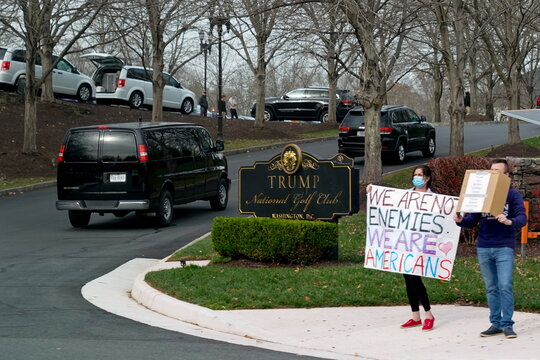 People hold signs as U.S. President Trump's motorcade arrives at the Trump National Golf Club