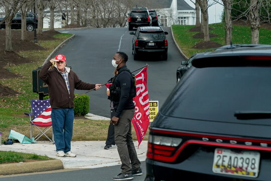 A supporter of U.S. President Donald Trump salutes the presidential motorcade as it arrives at the Trump National Golf Club