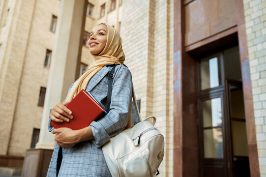 Arab girl with books poses at university entrance