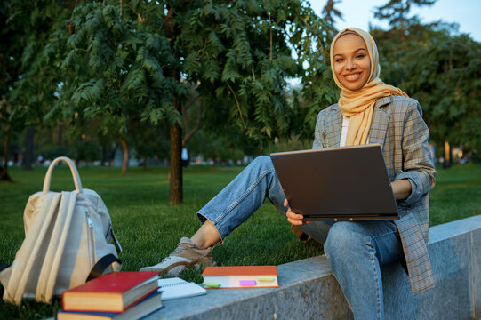 Arab female student in hijab using laptop in park