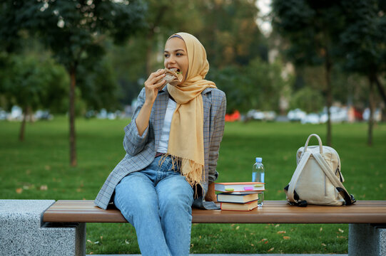 Arab female student sitting on the bench in park