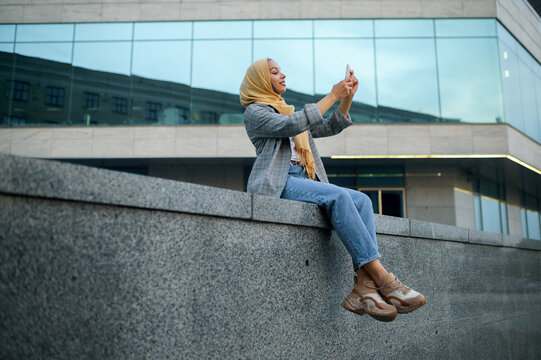 Arab girl makes selfie at the building in downtown