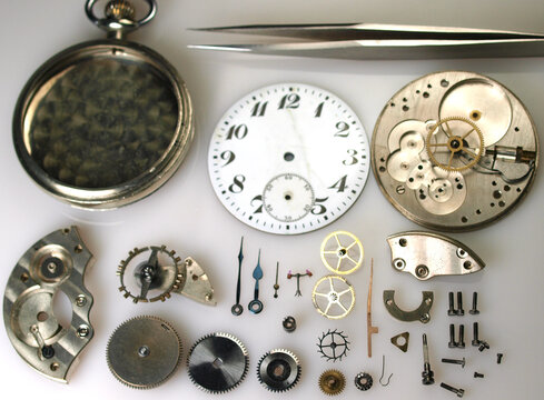display of parts of vintage watch mechanism: dial, gears, screws, balance wheel and springs