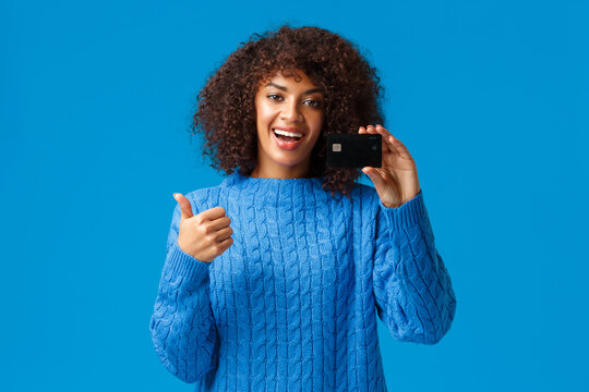 Satisfied young modern girl got bank account, opened deposit, using cashback service. Attractive african american woman in winter sweater, show thumbs-up and credit card in approval, recommend