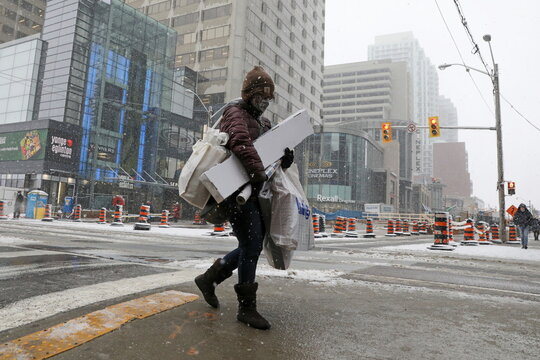 Shopper carries Christmas purchases a day before coronavirus disease restrictions are reintroduced in Toronto